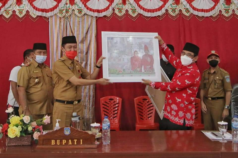 Pjs Bupati Bolsel Hi Praseno Hadi menerima cindera mata dari Bupati Bolsel Hi Iskandar Kamaru sebagai wujud apresiasi masyarakat dan Pemda Bolsel.