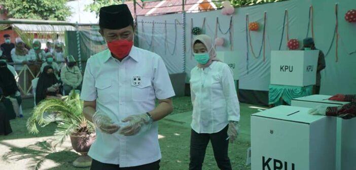Bupati Hi Iskandar Kamaru bersama istri di lokasi TPS I Desa Momalia Kecamatan Posigadan.