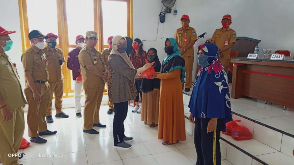 Ketua PKK Kabupaten Bolsel Titin Agustina saat menyerahkan paket bantuan sembako kepada masyarakat.